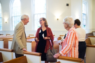 a small group of people talk and laugh standing between church pews