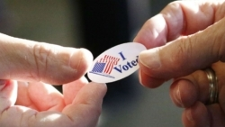 an image of two hands passing off a sticker that says i voted