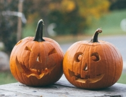 two carved jack-o-lanterns on a wood table in front of fall foliage