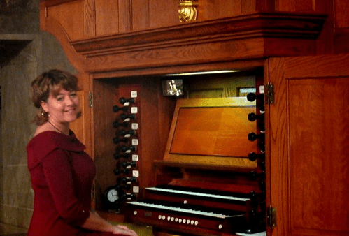 kim hess seated at a large traditional wood organ